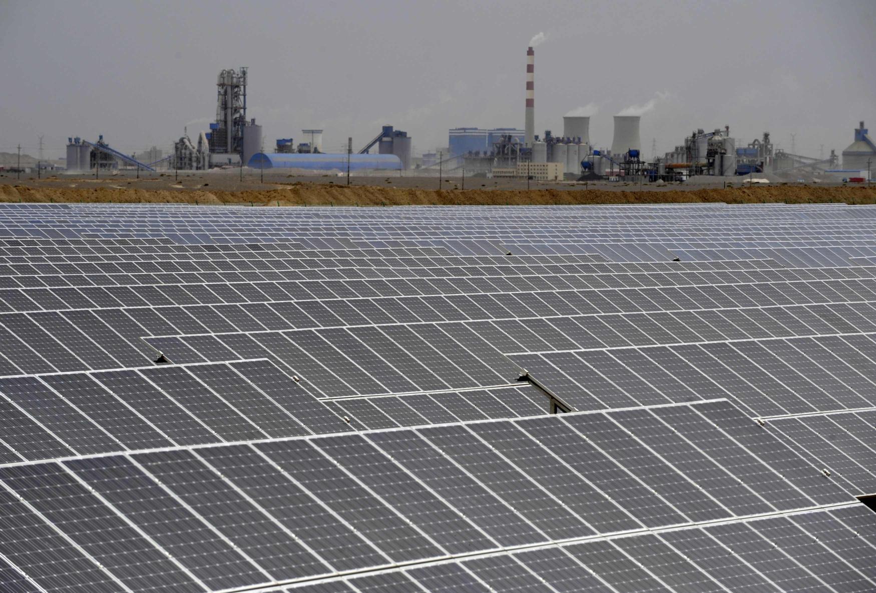 Una centrale solare, alle spalle una centrale termoelettrica ad Aksu in Xinjiang, Cina (Reuters)