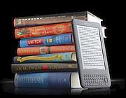 Un Kindle e i vecchi libri di carta (Ap)