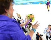 Phelps lancia alla madre Debbie i fiori ricevuti con l'oro nella 4x100 (Afp)