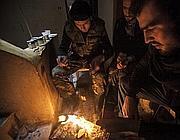 I ribelli siriani si scaldano intorno al fuoco dopo aver combattuto contro le forze lealiste (Ap)