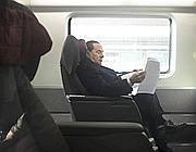 Berlusconi in treno mentre rientra a Milano (Ansa)