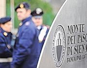 Carabinieri davanti alla sede della Banca Monte dei Paschi di Siena  (Ansa)