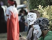 Militanti anti regime in Bahrain indossano la celebre maschera di Anonymous (Afp)