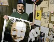 Felix DeJesus, padre di Gina, nel 2004 con un'immagine della figlia scomparsa (Ap)