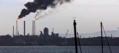 La fumata nera che lunedì 8 luglio si è sprigionata da una delle ciminiere dagli impianti della raffineria Eni di Taranto (Ingenito/Ansa)