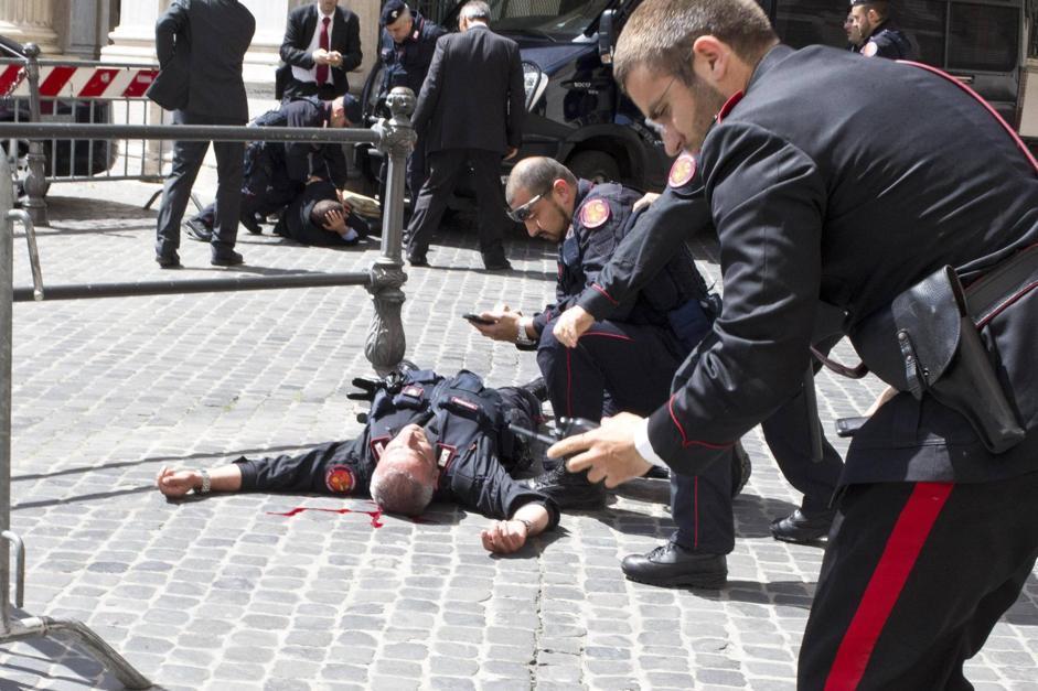 Nello scatto Giangrande, il brigadiere ferito al collo e, sullo sfondo, lo stesso Preiti a terra (Ansa/Percossi)