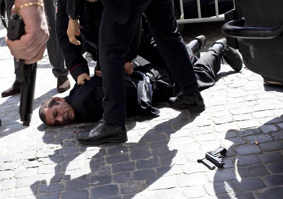 Luigi Preiti e la sua pistola a terra. Secondo il ministro dell'Interno Angelino Alfano «non è riuscito a suicidarsi perché aveva finito il caricatore» (Ansa/Percossi)