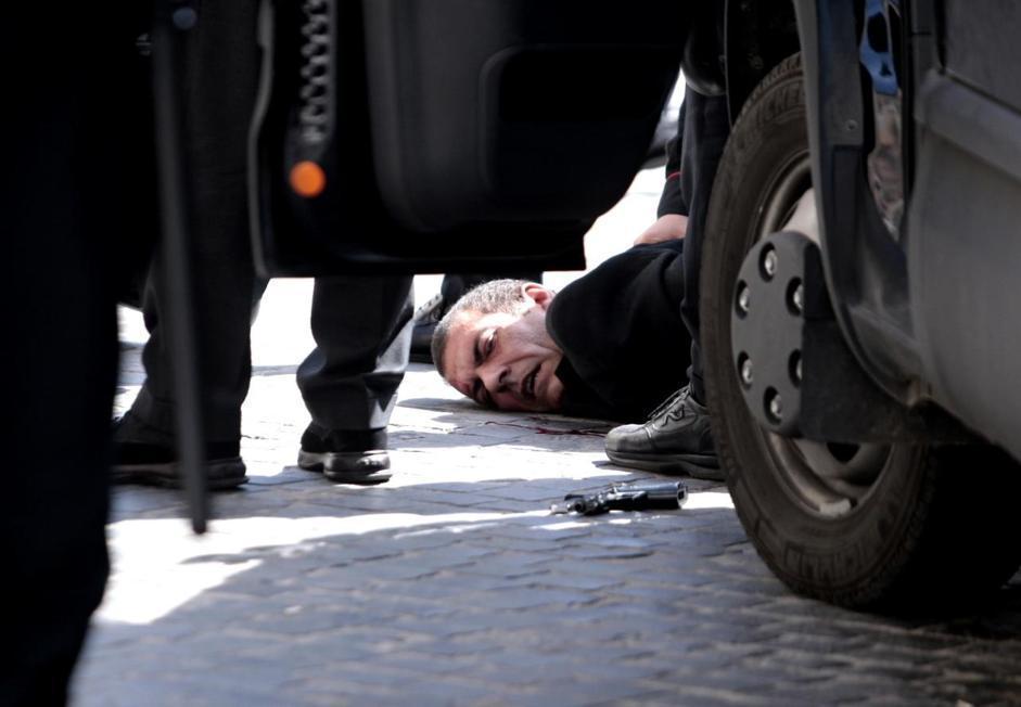 In primo piano la pistola di Luigi Preiti, sullo sfondo l'arrestato (LaPresse/Scrobogna)