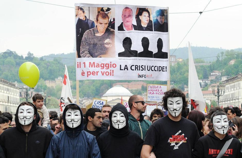 Lo striscione per Luigi Preiti davanti ad alcuni cartelli che reclamano il diritto alla casa («Tutti a dormire a casa di Cota», il governatore del Piemonte) (Ansa/Di Marco)