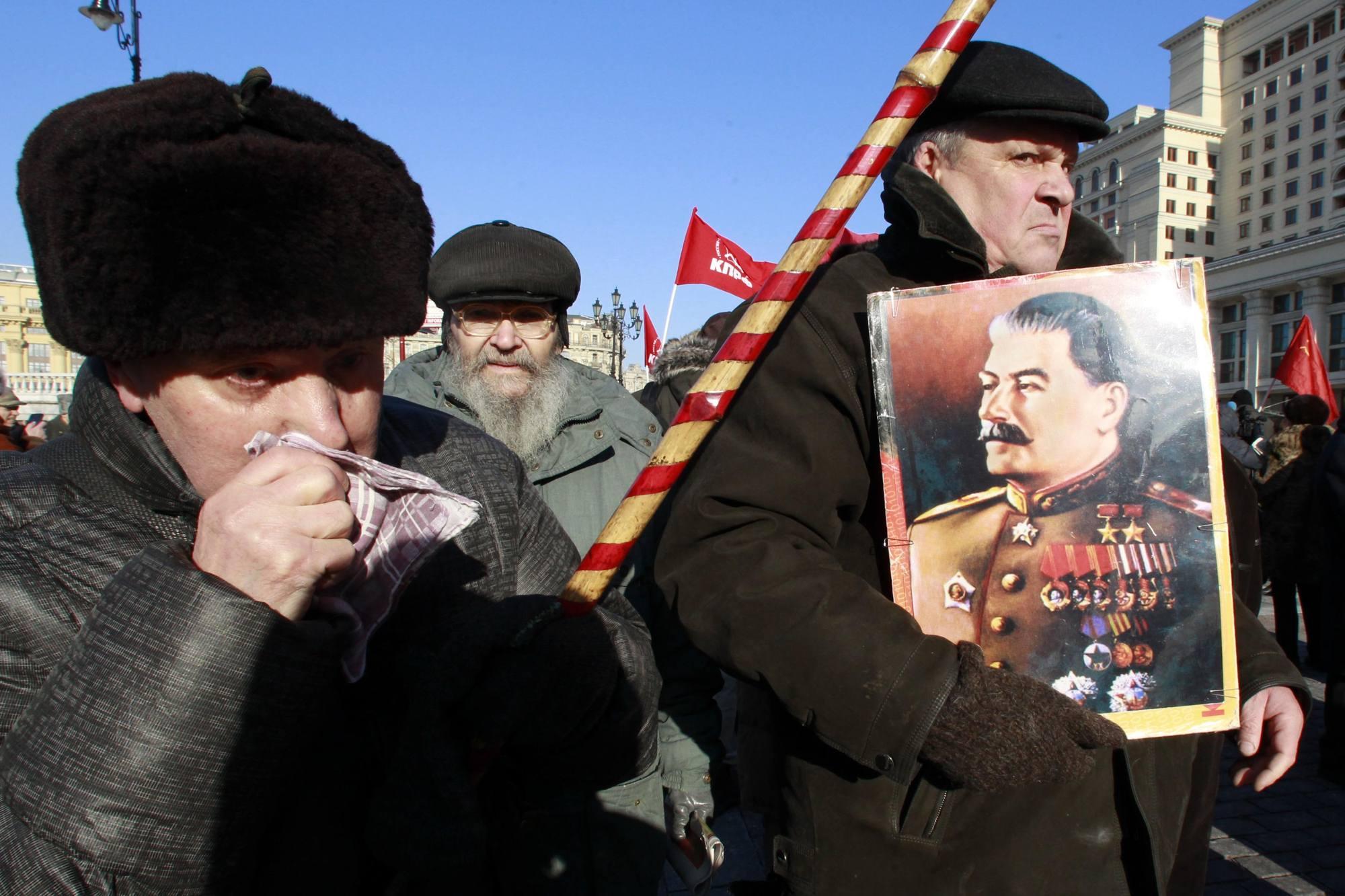 Nostalgici mostrano il ritratto di Stalin. L'opinone dei russi sul leader è sempre stata ambivalente: chi lo considera un feroce dittatore, responsabile del massacro di milioni di persone, e chi lo ritiene il salvatore della nazione, colui che ha permesso alla Russia di vincere la seconda guerra mondiale (Reuters/Karpukhin)