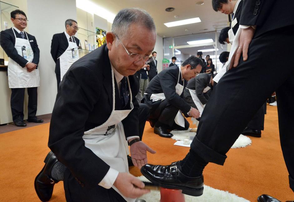 I dirigenti di una marca di lucido per scarpe fanno i sciuscià per i cinque nuovi assunti nella sede di Tokyo (Afp/Tsuno)