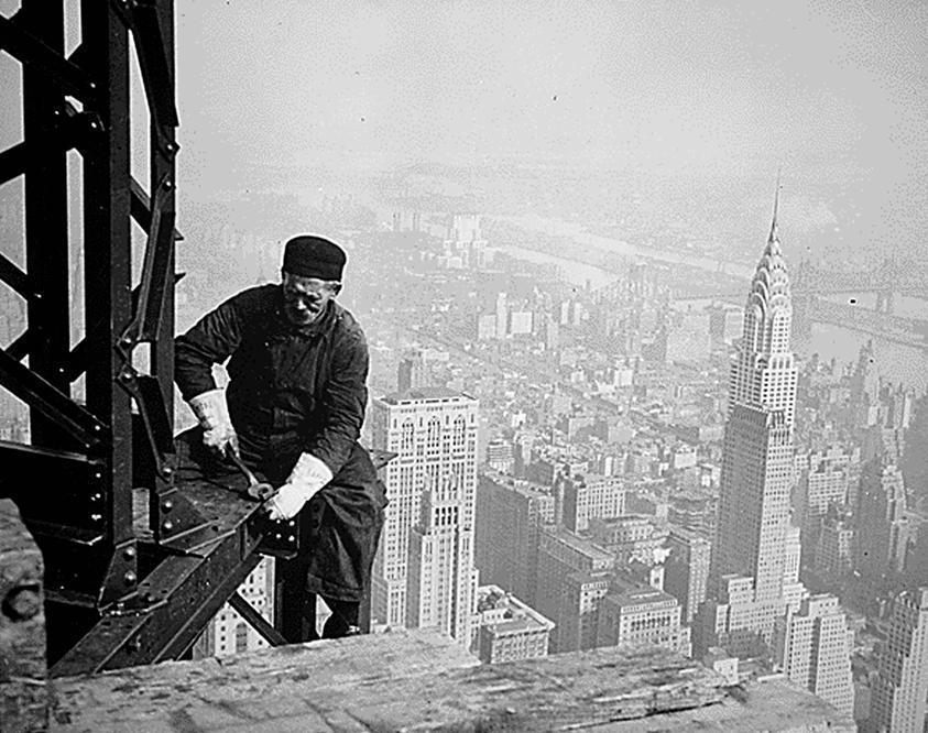 Un operaio al lavoro durante la costruzione del grattacielo. Sullo sfondo il «concorrente» Chrysler Building (Afp)