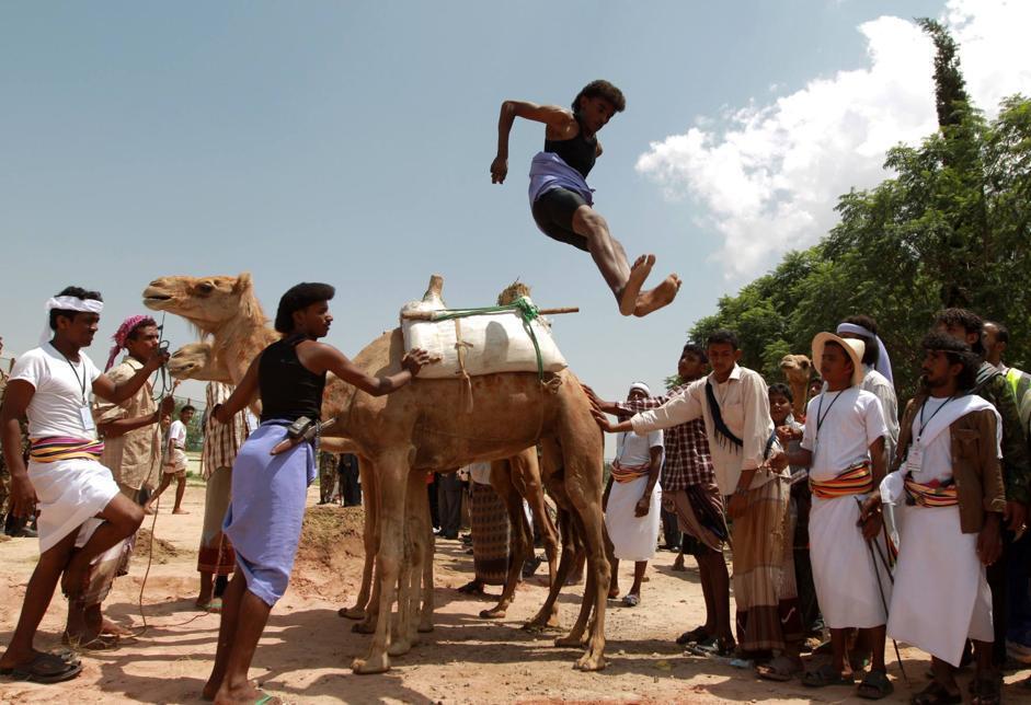 Acrobati si producono nel salto dei cammelli (in questo caso due cammelli) durante la cerimonia di apertura del Festiva d'Estate di Sanaa, la capitale dello Yemen (Afp/Huwais)