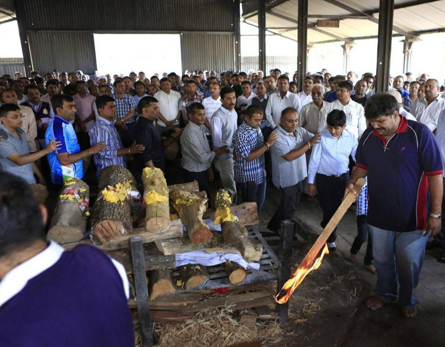 Il padre di Nehal Vekaria, indiana di 16 anni, accende il fuoco per la cremazione (Reuters/Khamis)