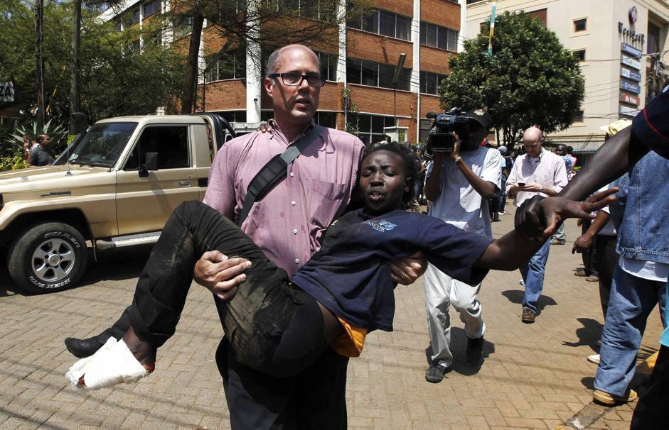 Un giornalista soccorre una donna rimasta ferita (Reuters/Mukoya)