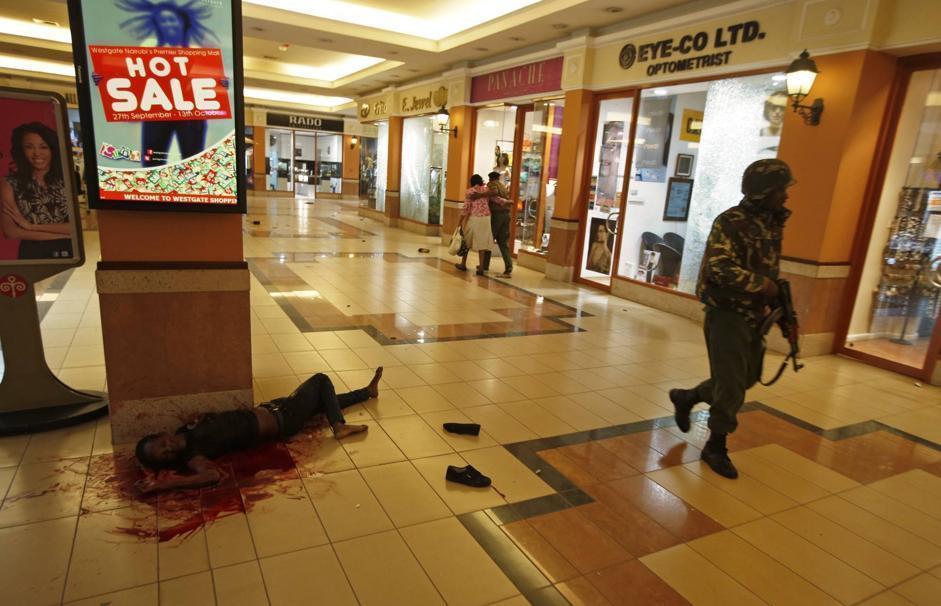 Il corpo di una donna al primo piano del palazzo. Sullo sfondo, due scampati al dramma si abbracciano mentre lasciano l'edificio (Reuters/Tomasevic)