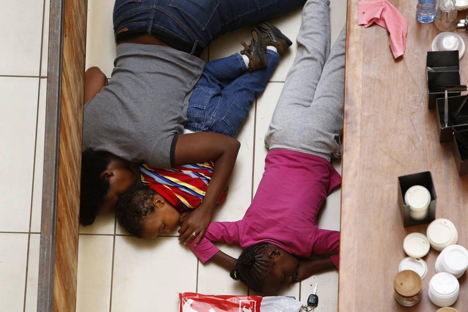 Intanto, ai piani alti qualcuno era ancora nascosto. Una donna e i suoi due figli dietro un bancone (Reuters/Modola)