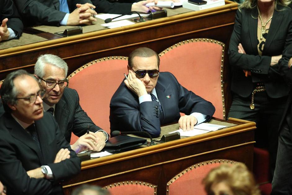 Silvio Berlusconi con gli occhiali da sole seduto sugli scranni dell aula del Senato (Ansa)