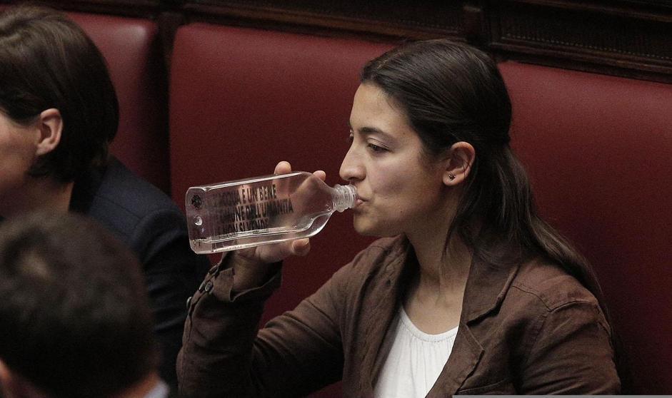 Federica Daga del Movimento 5 Stelle alla Camera, mentre beve da una bottiglia con una scritta contro la privatizzazione dell'acqua  (Giuseppe Lami/Ansa)