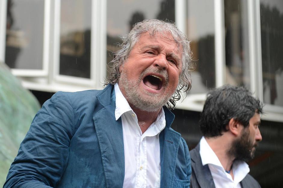 Comizio bagnato per Beppe Grillo, lunedì mattina, a Roma davanti alla sede Rai. Il comico ha parlato sotto la pioggia scrosciante  durante la manifestazione del M5S contro i vertici di viale Mazzini. «I giornalisti Rai sono camerieri dei politici», ha detto il leader del M5s. Grillo ha poi sollecitato i  precari «a ribellarsi». «La Rai è composta da 13 mila dipendenti con degli attributi così, ma non riescono a fare servizio pubblico perché la politica ha messo i propri camerieri e leccapiedi nei Tg», ha detto (Corbis)