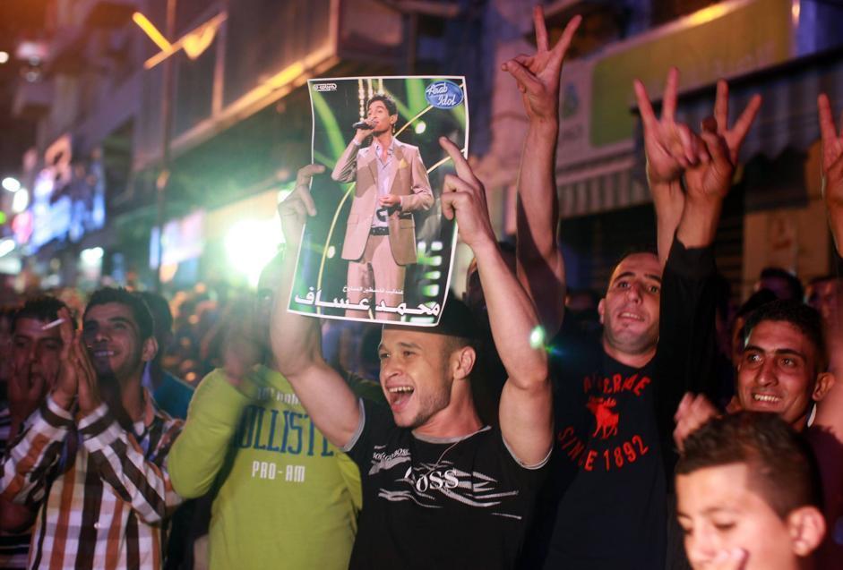 La gente a Ramallah esulta per la vittoria di Mohammad Assaf al talent «Arab Idol» e mostra le immagini del ragazzo. Il programma televisivo è stato seguito in strada sui maxischermi allestiti per l'evento (Afp/Momani)