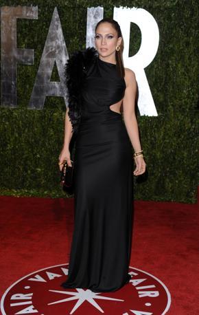 Nera e serissima Jennifer Lopez che al party di Vanity Fair ha scelto un abito asimmetrico che le lascia scoperta una parte della schiena. alla premiazione invece era tutta in bianco. Ma l'espressione sul viso era la stessa (Ap)