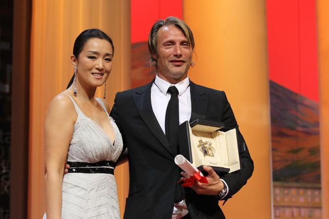 "L&#39;attore danese Mads Mikkelsen con la cinese Gong Li dopo aver ricevuto il premio di miglior attore per ""The Hunt"" (Afp)"