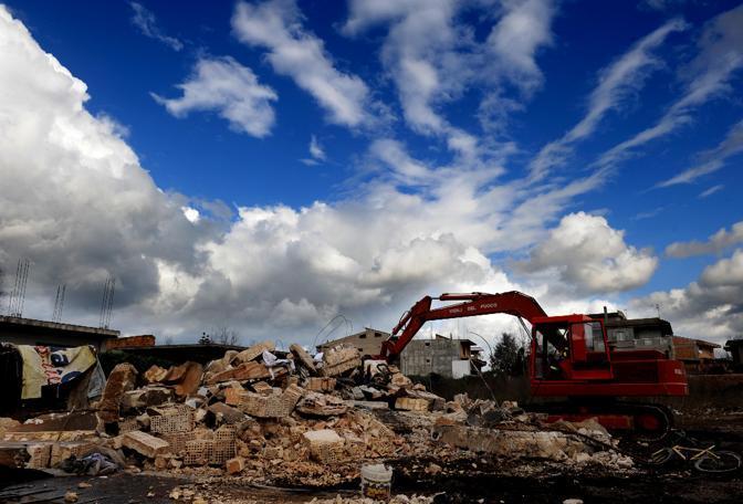 A Rosarno è cominciata la demolizione degli accampamenti usati dagli immigrati: ruspe in azione nelle ex fabbriche trasformate in dormitori, Rognetta e Opera Sila (Ansa)