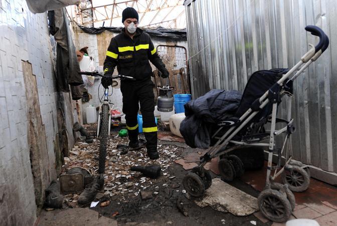 Un vigile del fuoco tra le baracche occupate dagli immigrati nell'ex deposito alimentare Rognetta (Ansa)