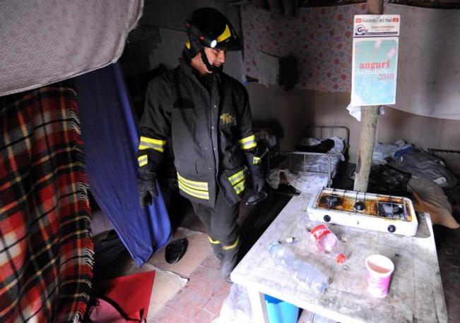 L'interno delle baracche occupate dagli immigrati nell'ex deposito Rognetta (Ansa)