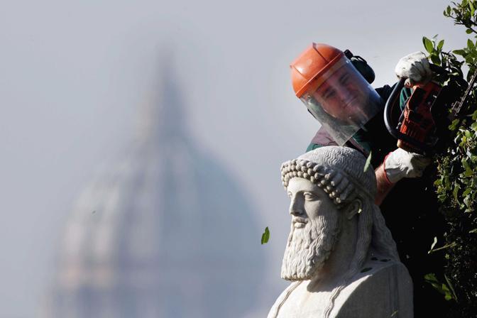 Roma, ore 11.37 - Simone Checconi, giardiniere di Villamedici, pota una siepe dei giardini dell?Accademia di Francia a Trinità de?Monti. Sullo sfondo la cupola di San Pietro - Foto di Franco Origlia