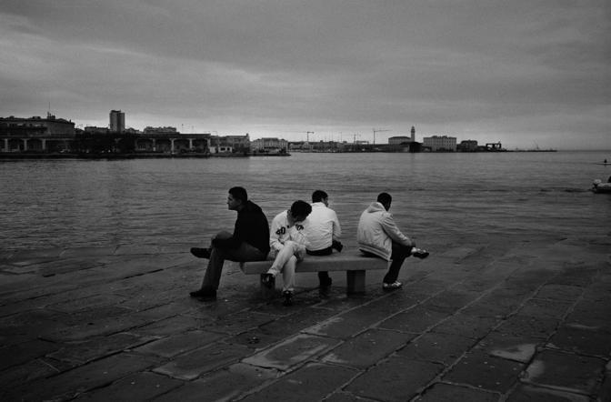 """Trieste, ore 16.59 - Altramonto, ragazzi seduti su una panchina del molo """"audace"""" - Foto di Ivo Saglietti"""