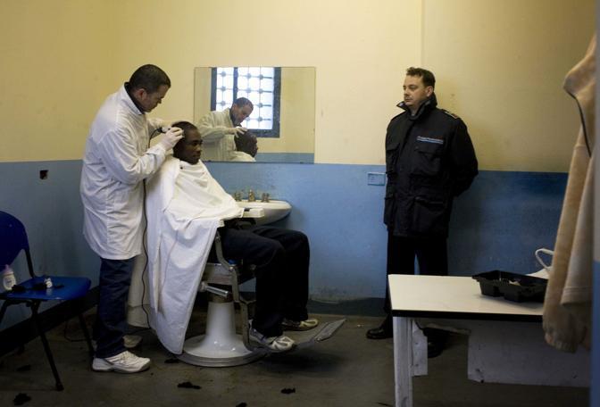 Pesaro, ore 10.45 - Il barbiere della seconda sezione del carcere taglia i capelli a un detenuto appena arrivato - Foto di Alberto Giuliani