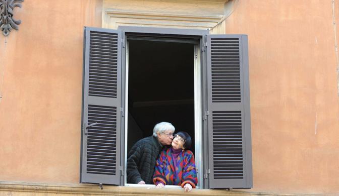 Roma,ore 14.34 - Il regista Gigi Magni e la costumista Lucia Mirasole si baciano dolcemente alla finestra della loro casa in Via del Babuino - Foto di Rino Barillari