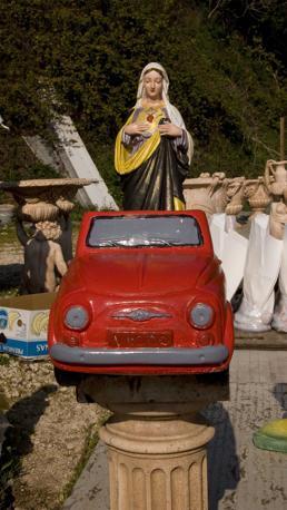 Velletri (roma), ore 11 - Lungo la via Appia, al bordo della strada, tra nani, auto e cupidi in cemento armato svetta una madonna, pure lei in cemento - Foto di Giovanni Cozzi