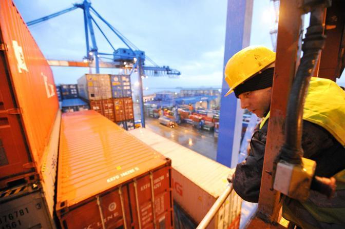 Genova, ore 7.50 - Primo turno a 45 metri d'altezza, un lavoratore rimuove i blocchi di una nave ormeggiata al terminal sech - Foto di Davide Pambianchi