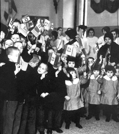 Festa di Natale in una scuola durante il fascismo: i bambini indossano la camicia nera