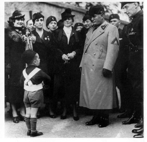 Mussolini salutato da un bambino in divisa da Balilla