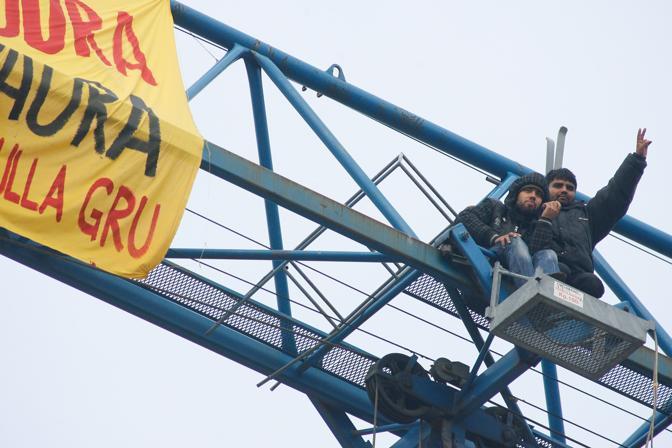 Gli immigrati asserragliati su una gru a Brescia dal 30 ottobre
