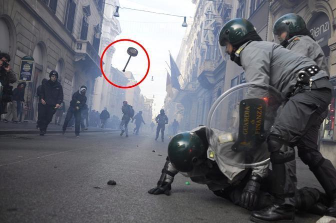 Roma, scontri tra dimostranti e reparti anti-sommossa della Guardia di Finanza. Nel tondo quello che sembra uno dei cartelli divelti dai dimostranti e utilizzati come proiettili contro le forze dell'ordine.