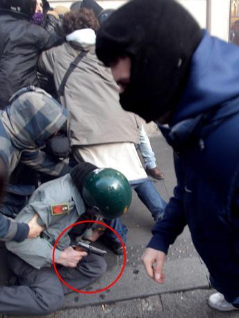 Roma, scontri tra dimostranti e reparti anti-sommossa della Guardia di Finanza. Nel tondo la pistola impugnata da un finanziere finito a terra durante gli scontri.