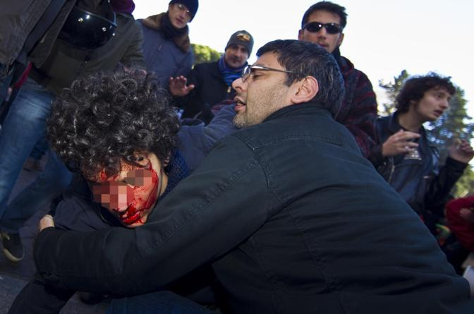 Francesco Caruso soccorre Cristiano il ragazzo colpito al voto con un casco durante la manifestazione contro il governo del 14 dicembre a Roma (Ansa)