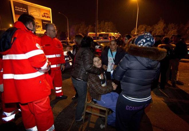 La mamma dei 4 bambini vittime del rogo viene rincuorata dai soccorritori (Ansa/Percossi)