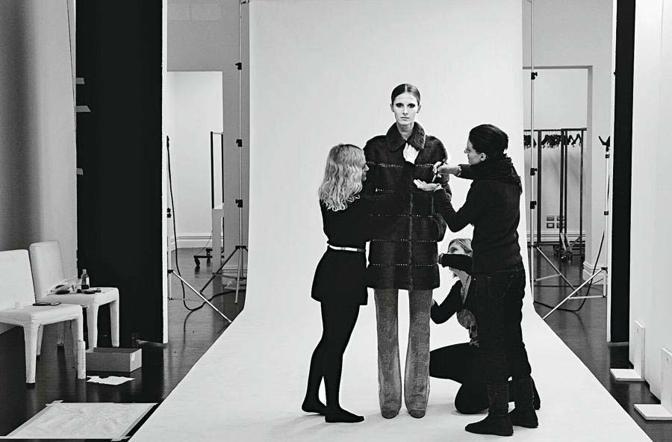 Un fondale bianco, una modella, tre stylist che «aggiustano» il capo su di lei, preparandola per lo scatto di una foto destinata al lookbook dedicato alle pellicce della maison Valentino - Foto di Stefano Guindani