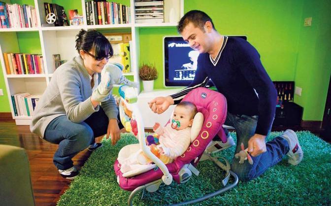 Aulon Begaj e la compagna Federica Brignoli giocano con la figlia Aurora, di 4 mesi. Aulon è albanese. è arrivato in italia con un «barcone della speranza» nel 1999, quando aveva 19 anni. Oggi lavora come pizzaiolo in un locale milanese - Foto di  Alessandro Grassani