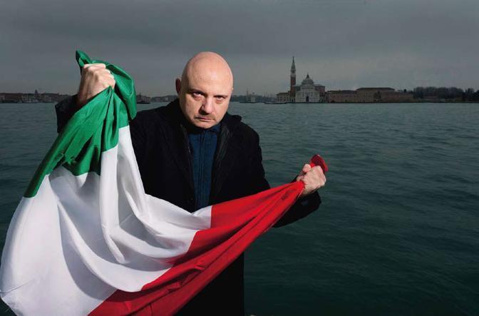 Lo scrittore Tiziano Scarpa, romanziere, poeta, autore teatrale, che nel 2009 vinse il premio Strega con il suo «Stabat mater», stringe una bandiera tricolore. Nell?anniversario dei 150 anni dell?Unità, è diventata il simbolo delle sue battaglie contro il razzismo - Foto di Graziano Arici