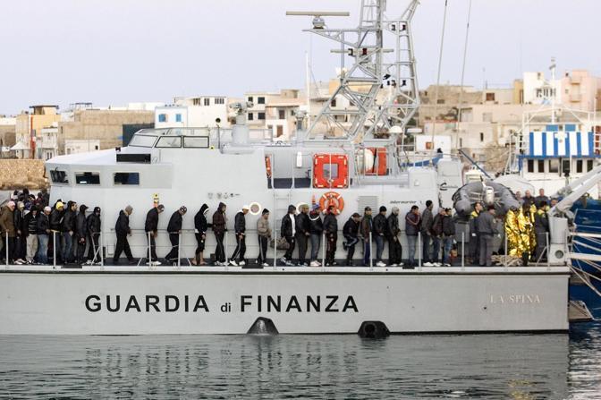 Extracomunitari sulla motovedetta della Guardia di Finanza al molo Favarolo nel porto di Lampedusa (Ansa)