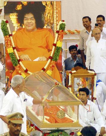 Il corpo di Sai Baba esposto per l'ultimo saluti dei fedeli all'ashram di Puttaparti, in India (Reuters)