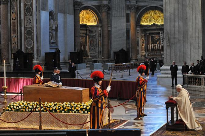 Ratzinger si inginocchia davanti al feretro di Giovanni Paolo II (Afp)