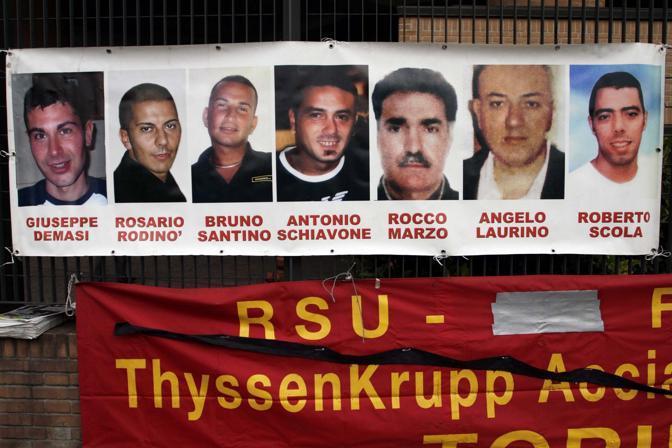 Uno striscione fuori dal tribunale con i volti degli operai morti (Fotogramma)